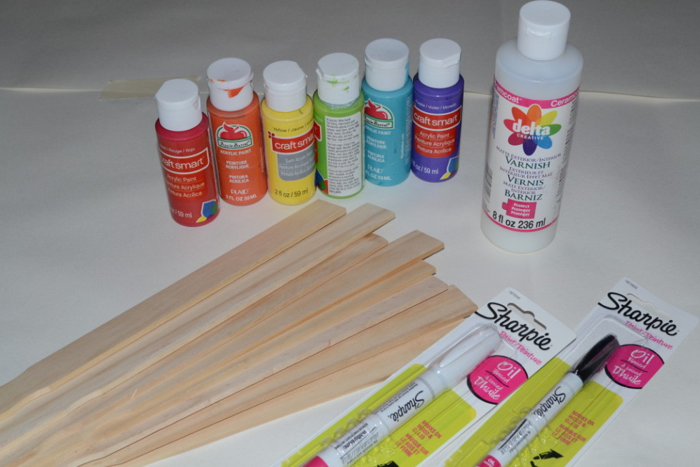 You will need paint stirrers, paint, sealant, paint pens, and paint brushes to make a rainbow of plant markers.