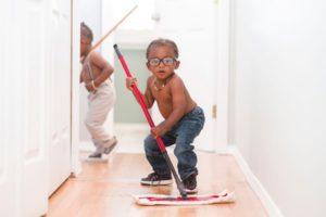 Two little boys cleaning a hallway with a mop