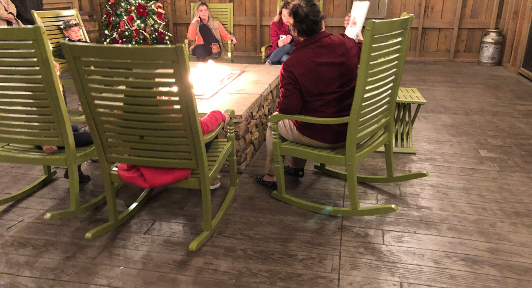 A young woman reads to children sitting in rocking chairs around a gas fire table