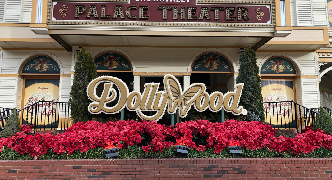 The Dollywood sign under the Palace Theatre surrounded by blooming red flowers