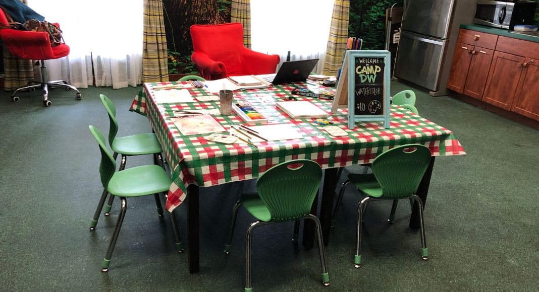 Green chairs are arranged around a checkered tablecloth in Dollywood's Camp DW room