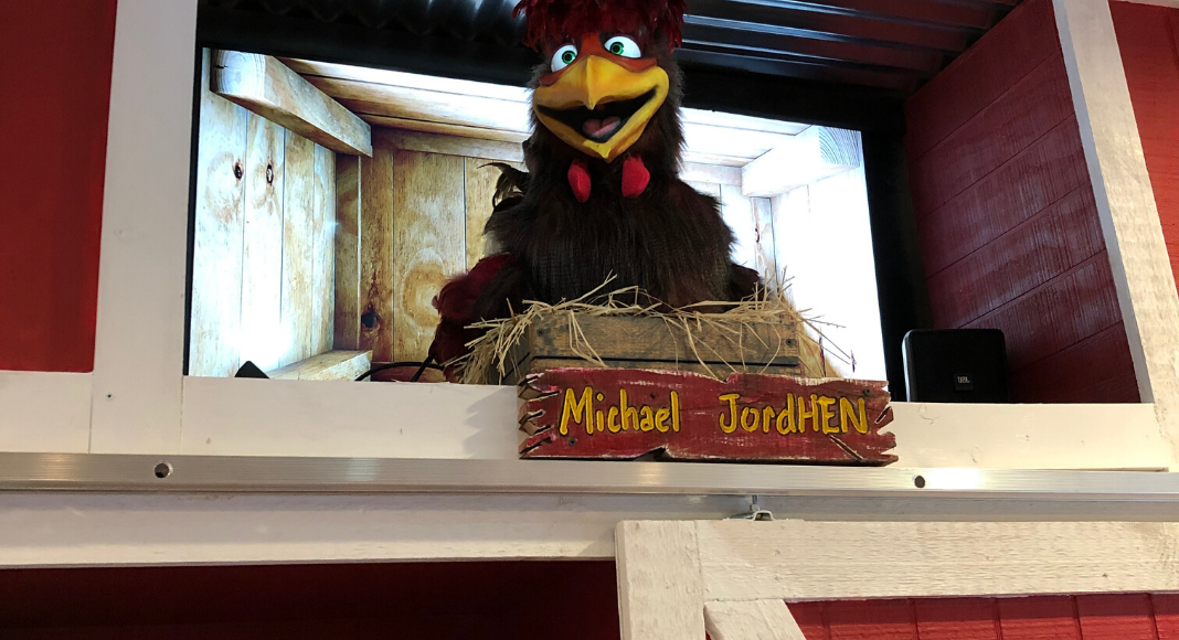 Large animatronic chicken smiling with tv screen of a henhouse behind it named Michael JordHEN from Frizzle Chicken Farmhouse Cafe