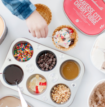 A child's hand celebrating Valentin's Day reaching over a muffin tin full of ice cream toppings surrounded by Hudsonville Ice Cream tubs with an ice cream scooper.