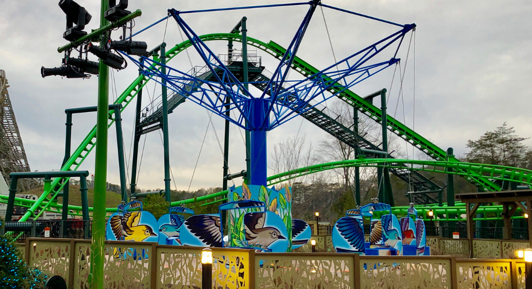A flying bluebird children's ride in front of a Steele roller coaster at Dollywood Amusement Park