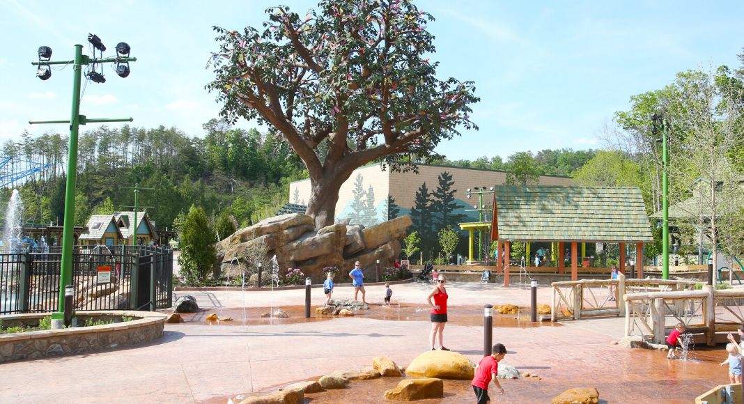 Children playing in the summer sun at the Wildwood Grove Creek at Dollywood Amusement park with the Wildwood tree in the background for kids to visit with their Pre-K Imagination season pass