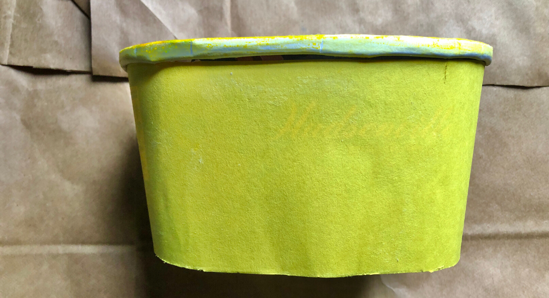 An empty Hudsonville Ice Cream carton covered in yellow construction paper.