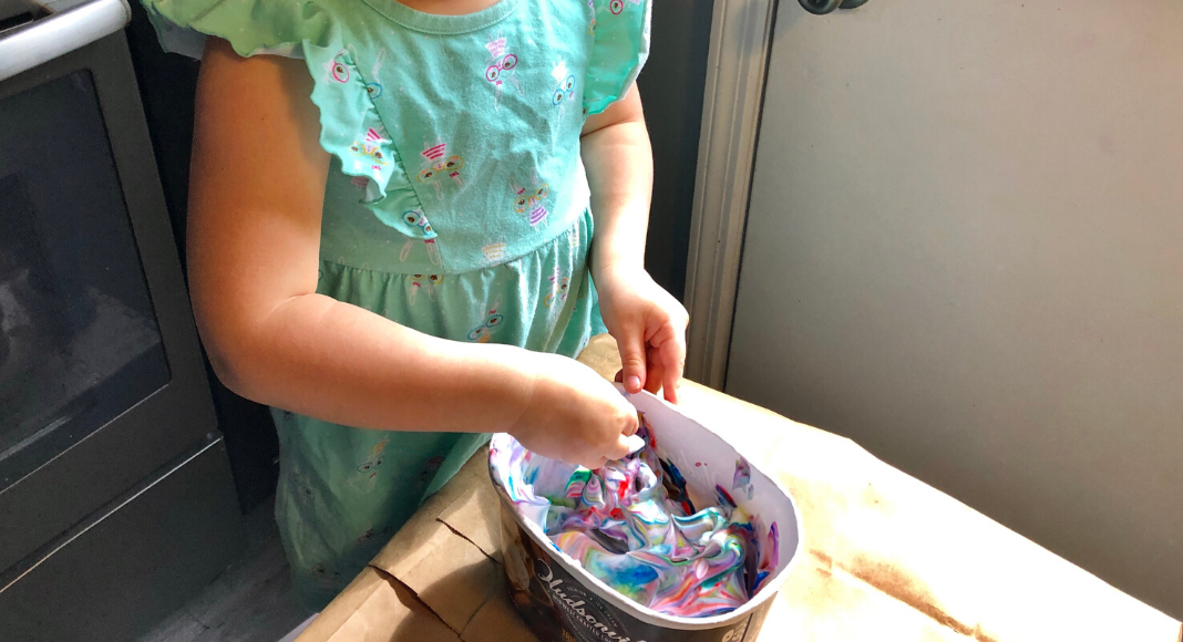 A child in a bunny dress swirling food coloring into whipped topping in an empty Hudsonville Ice Cream container