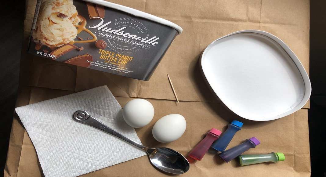 A table with hard boiled eggs, food coloring, a spoon, and an empty Hudsonville Ice Cream container.