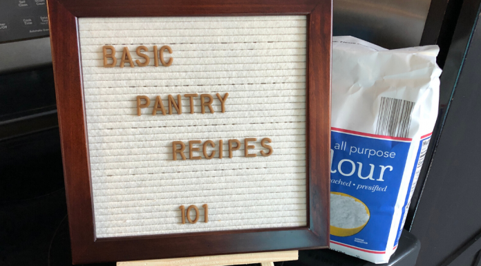 "A letter board sign in front of a bag of flour saying ""Basic Pantry Recipes 101"""