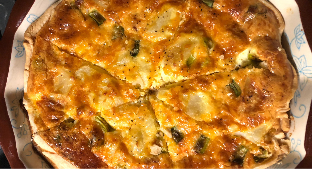 A fresh quiche made with homemade pie crust, potatoes, bacon, cheese, and green onions.